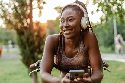 Photo of a young African American woman leaning on her bicycle using a mobile phone and wireless hea...