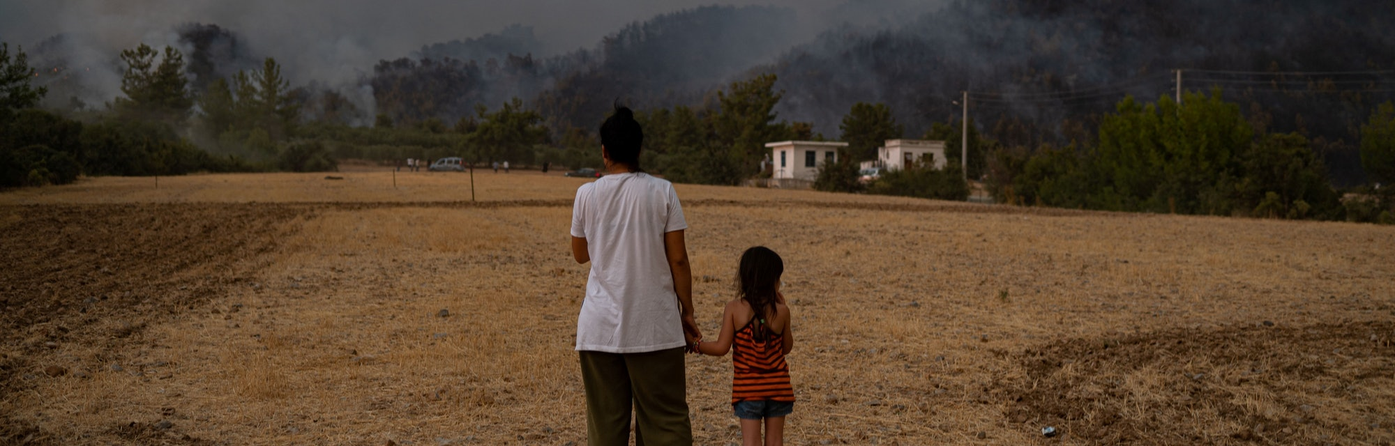 TOPSHOT - A woman and child stand in a field as they watch wildfires as they burn in Koycegiz distri...