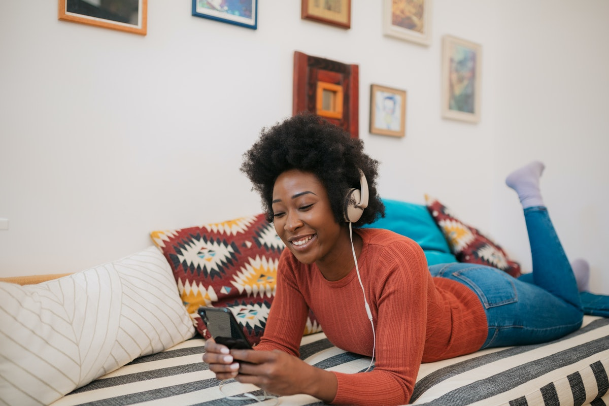 Young cheerful African American woman relaxing at home, using a smart phone to listen to music and s...
