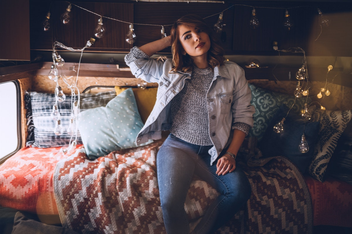 Beautiful Young Blond Woman Resting In Camper and Christmas Decorative Lights She Arranged