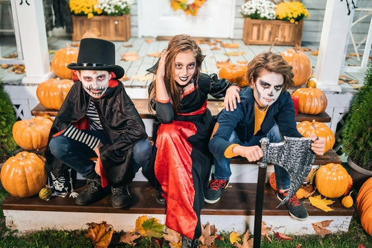 Kids dressed in Halloween costumes sitting on the stairs