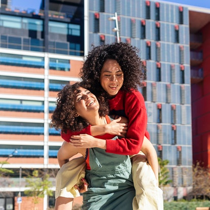 two female friends smiling as one gives the other a piggy back ride as they chat about leo libra fri...