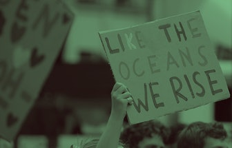 """Climate activists hold a placard reading """"Like the oceans we rise""""during a demonstration called by F..."""