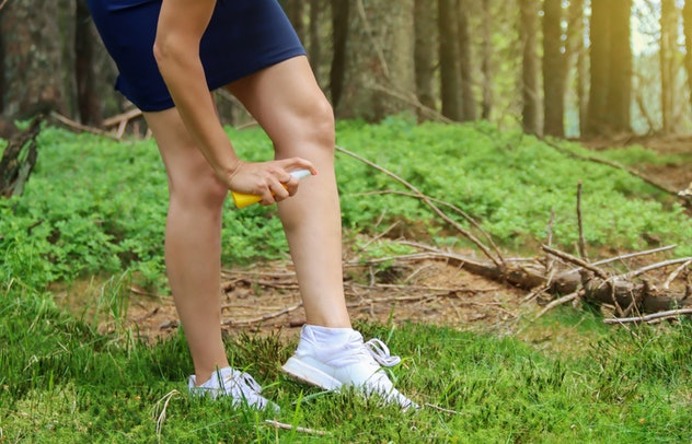 woman applying bug spray to her leg in the forest
