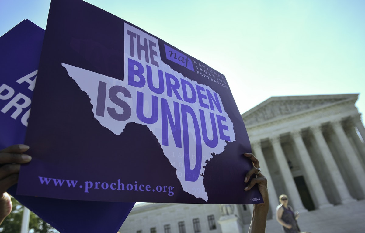 An abortion rights activist holds placards outside of the US Supreme Court before the Court struck d...