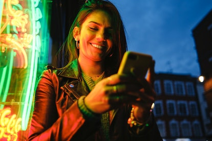 Young woman texting in neon lights during Mercury retrograde fall 2021, which will affect her zodiac...