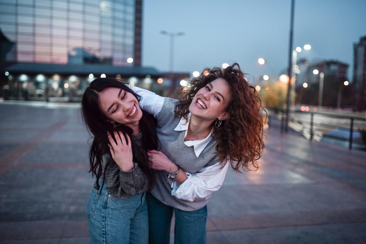 Belas mulheres abraçando andando fora do prédio de apartamentos à noite