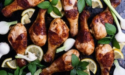 Roasted chicken legs with lemon slices. onion, garlic and basil herbs on rural baking tray viewed fr...