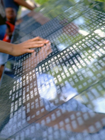 Memorial wall  overlooking New York City.  A hand touches the names of victims of September 11.  See...
