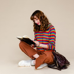 A portrait of a happy young woman sitting on a floor reading a book with her backpack in front of pl...