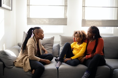 Image of two adults and an older child sitting on a couch talking.