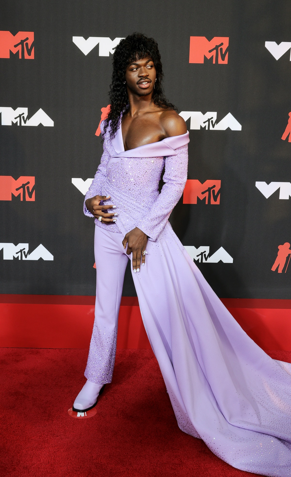 Lil Nas X attends the 2021 MTV Video Music Awards in a lavender suit-and-dress combo and curly mulle...