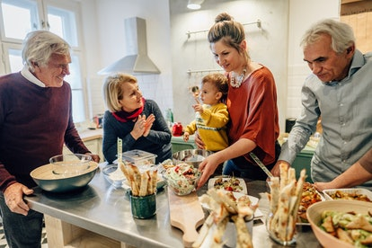 Photo of a multi-generation family preparing Thanksgiving dinner in their kitchen