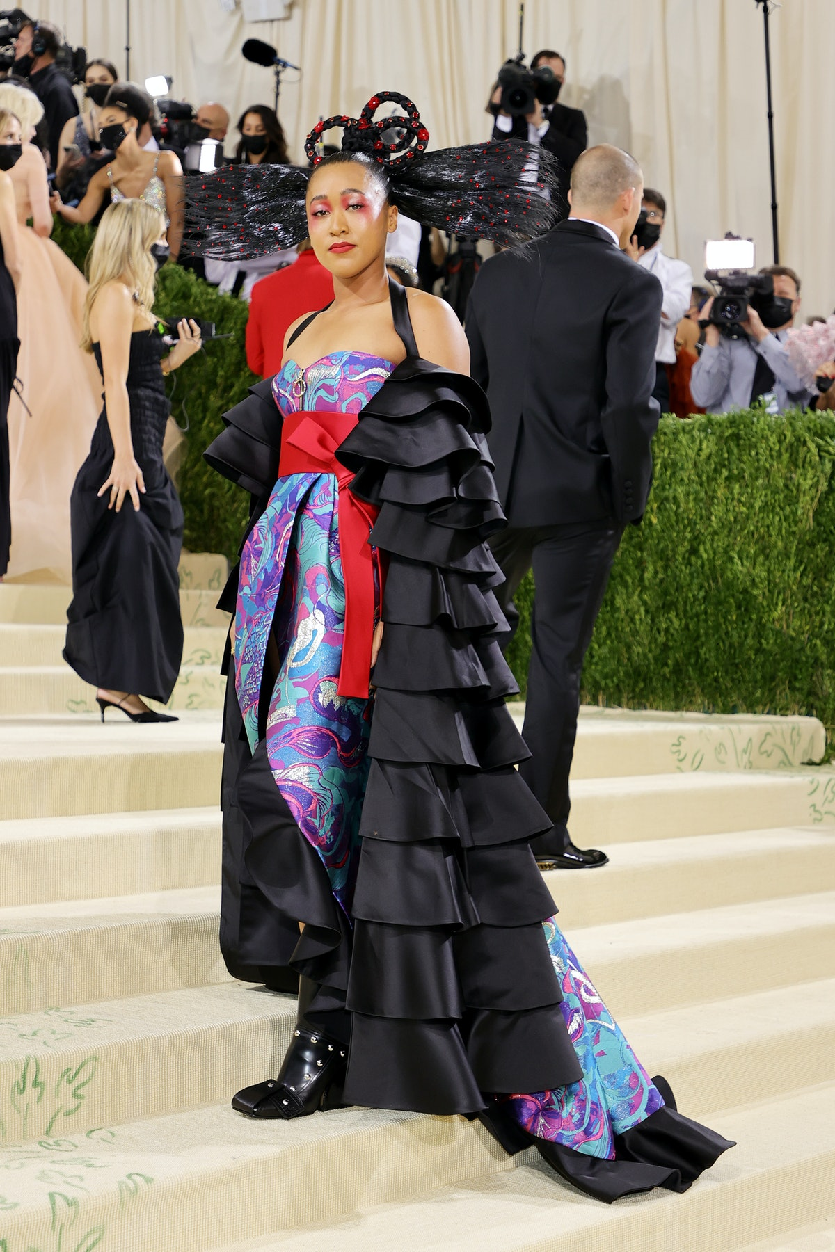 Naomi Osaka posed at the 2021 Met Gala in a colorful Louis Vuitton gown and a memorable hairstyle.