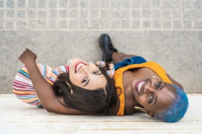 From above of multiethnic lesbian couple in trendy summer clothes standing near wall in city street