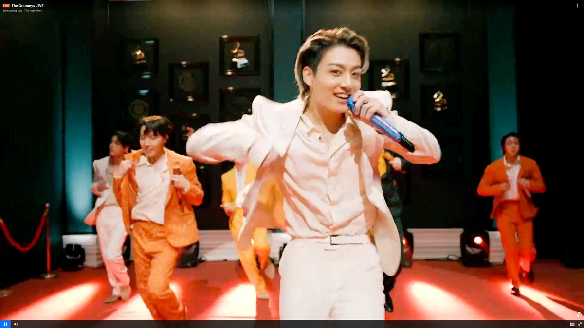 Jungkook of BTS performing at the 2021 GRAMMY Awards, before he wore coiffed hair at the 2021 VMAs.