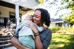 Mother holding toddler in front of new home