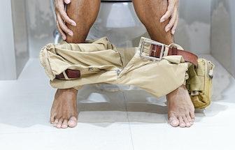 Man wear yellow pants sitting in toilet
