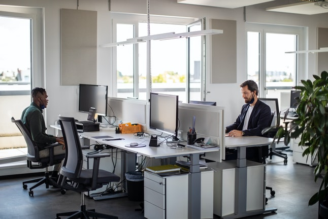 Shot of a business people working in office. Two businessman sitting apart from each other and worki...