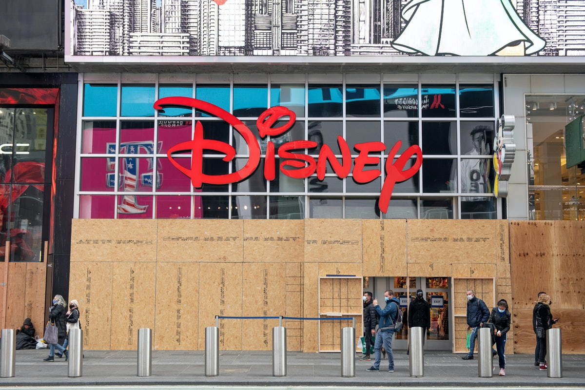 NEW YORK, NEW YORK - NOVEMBER 03: People wearing masks walk past the Disney Store in Times Square on...