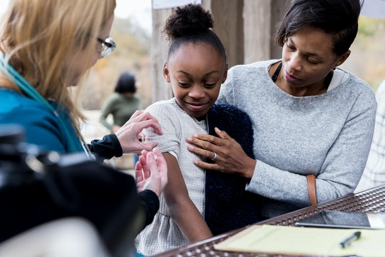 Young girl is consoled by her mom as she receives a flu shot at an outdoor free clinic.