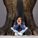 American director Steven Spielberg poses between a pair of giant dinosaur feet in a publicity still ...