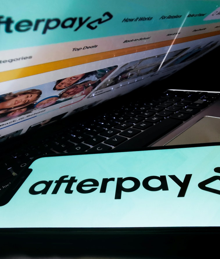 Afterpay logo displayed on a phone screen and Afterpay website displayed on a laptop screen are seen...