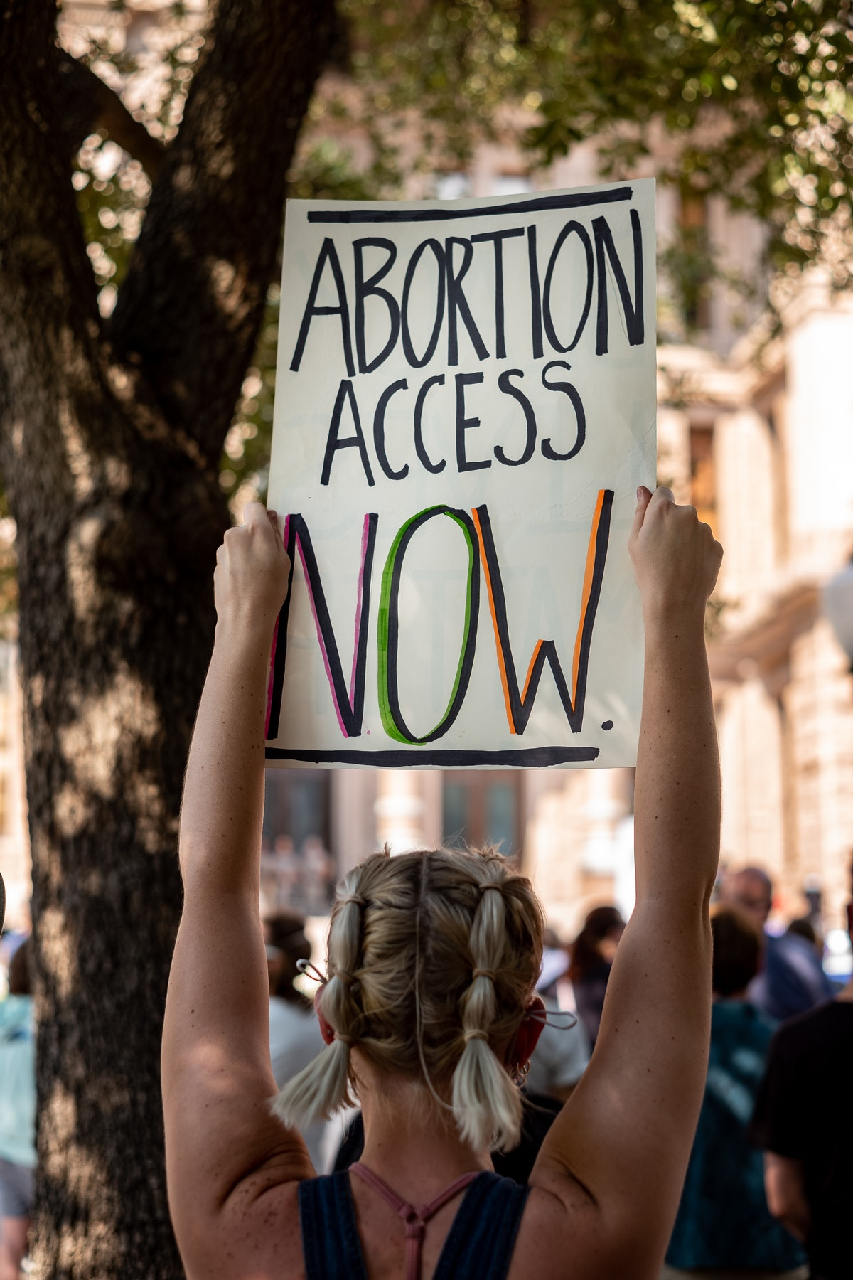 A woman carries a sign calling for access to abortion at a rally at the Texas State Capitol on Septe...