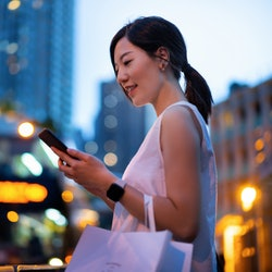 Young Asian woman using smartphone while walking down in city street against illuminated street ligh...