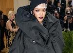 Rihanna attends the Met Gala wearing an all black jacket dress combination.