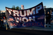Former US President Donald Trump supporters are seen as a motorcade with US President Joe Biden arri...