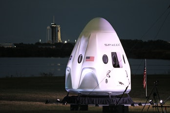 A full-size model of the Crew-1 spacecraft module sits near the launch pad as a SpaceX Falcon 9 rock...