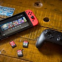 In this photo illustration, a turned on Nintendo Switch with 2 Joy-Con attached on it, a Pro Control...