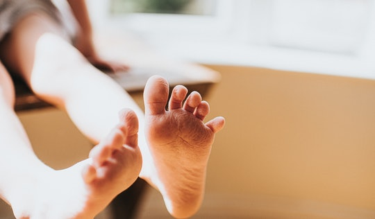 Cute little bare feet hanging off the side of a chair in sunny room. Skin wrinkled after having a ba...