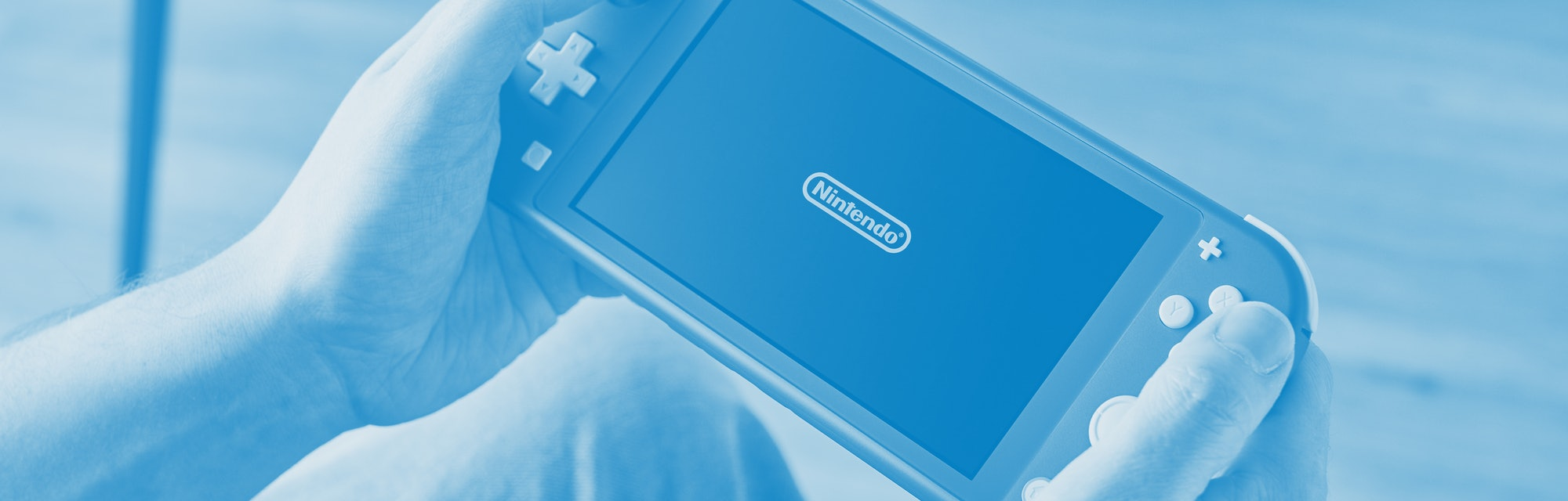 Detail of a person holding and playing a 2019 Nintendo Switch Lite handheld video games console with...