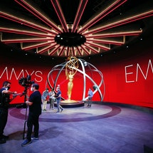 A behind the scenes shot of a giant Emmys statuette.