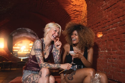 two women smiling together as they share a drink and chat about each sign's go to drink