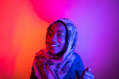 Portrait of a beautiful woman wearing a hijab, under neon lights; studio shot, isolated.