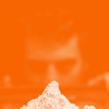 A guy looking at a heap of cocaine from a distance