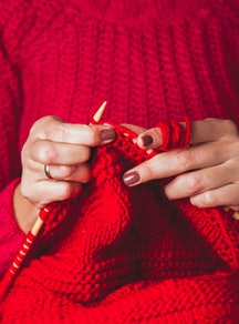 A woman in a red sweater knits a red sweater. Experts and women who've done it share tips for findin...