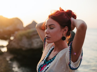 Young woman with long red hair enjoys beautiful sunset during the October 2021 new moon in Libra, wh...