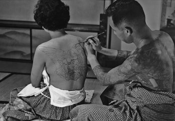 Tattoo artist Horigoro at work on a design on a woman's back in Japan in 1955. (Photo by FPG/Getty I...