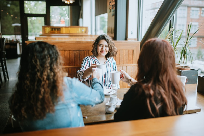 Three new friends have coffee at a diner. Experts share their tips for how to make friends in a new ...