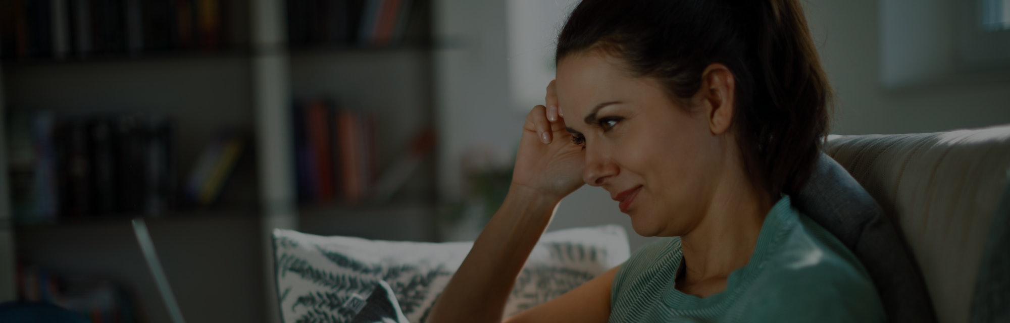 Smiling relaxed woman resting on couch using laptop