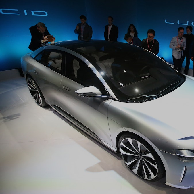 """Journalists look over the new """"air"""" electric car by Lucid Motors Inc. on Wednesday, Dec. 14, 2016, i..."""