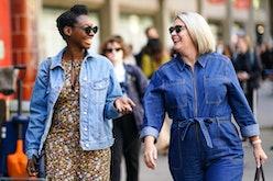 LONDON, ENGLAND - SEPTEMBER 13: A guest (L) wears sunglasses, a blue denim jacket, a floral print ju...