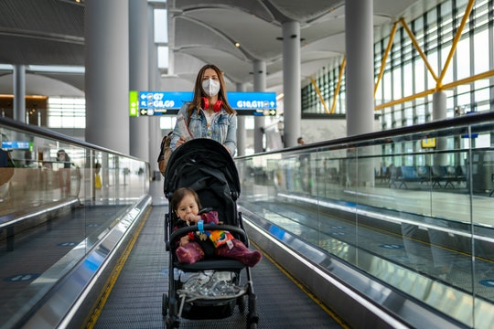 Young Woman traveling with her baby wearing a face mask during the COVID-19