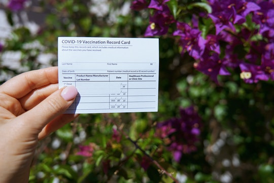 Woman holding covid-19 vaccination record card outdoors