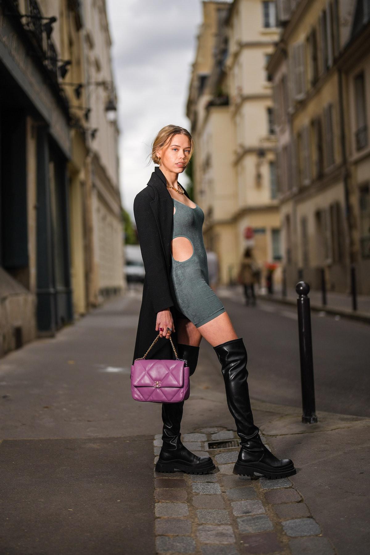 Almuneda Lapique wears gold earrings, a gold chain necklace, a long black Prada coat, a gray Zara sh...