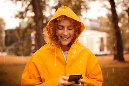 Happy young woman in yellow raincoat having fun on a rainy day in nature